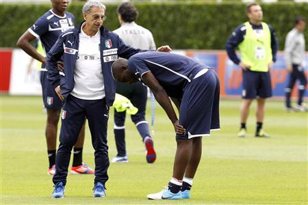 Italy's national soccer player Mario Balotelli (C) bends over as he talks with doctor Enrico Castellacci after picking up an injuring during a training session in preparation for Euro 2012, in Coverciano, near Florence, June 4, 2012. REUTERS/Giampiero Sposito