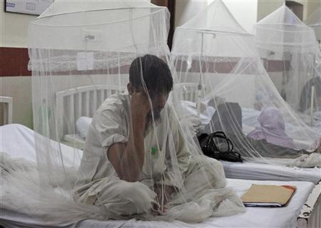 Mohammad Zubair, a 25-year-old man suffering from dengue fever, sits under a mosquito net while seeking treatment at the Services Hospital in Lahore September 18, 2011. REUTERS/Mohsin Raza
