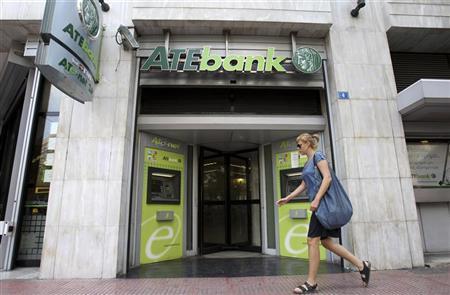 A woman walks in front of a branch of ATEbank in Athens July 23, 2010. REUTERS/John Kolesidis