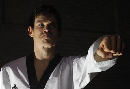 British Tae Kwon Do champion Aaron Cook poses for photos during a break in filming a promotional film at a location in central London, March 20, 2012. REUTERS/Andrew Winning