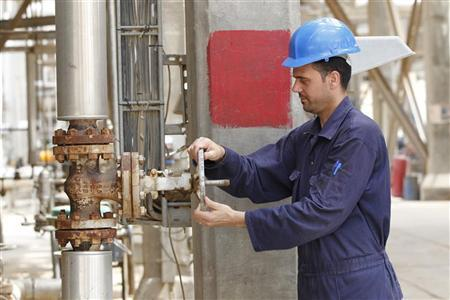 A worker adjusts the valve of an oil pipe of al-Doura refinery in Baghdad April 9, 2012. REUTERS/Mohammed Ameen
