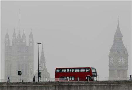 A bus crosses Waterloo bridge in front of the Houses of Parliament during a misty morning in London April 13, 2012. REUTERS/Luke MacGregor
