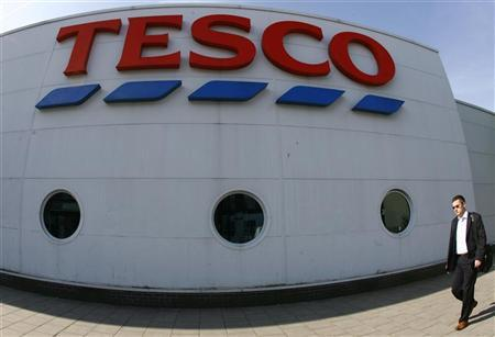 A pedestrian passes a Tesco store in central London June 9, 2008. REUTERS/Luke MacGregor (BRITAIN)