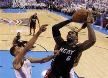<p>LeBron James (à droite), du Miami Heat, aux prises avec Thabo Sefolosha, de l'Oklahoma City Thunder. Le Heat a égalisé à une victoire partout en finale de la NBA en battant jeudi soir le Thunder 100-96 sur son parquet au terme d'un match au final exceptionnel. /Photo prise le 14 juin 2012/REUTERS/Jim Young</p>