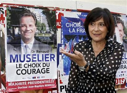 Marie-Arlette Carlotti, France's Socialist party candidate for legislative elections walks past a campaign poster of her opponent UMP party candidate Renaud Muselier as she leaves a voting station in Marseille, June 17, 2012. REUTERS/Jean-Paul Pelissier