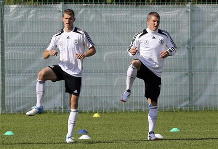 Germany's national soccer player Lars Bender and Bastian Schweinsteiger (R) warm-up during a training session ahead of the Euro 2012 in Gdansk, June 6, 2012. REUTERS/Thomas Bohlen