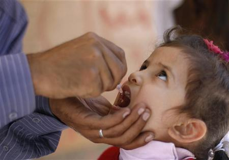 A girl receives a drop of polio vaccine at a health center in Sanaa January 9, 2012. REUTERS/Khaled Abdulah