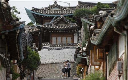 A couple take a picture at Bukchon Hanok Village, a traditional village in Seoul June 5, 2012. REUTERS/Kim Hong-Ji