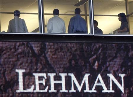 People stand next to windows above an exterior sign at the Lehman Brothers headquarters in New York in this September 16, 2008 file photo.REUTERS/Chip East/Files
