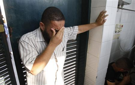 A Palestinian man reacts at a hospital morgue in Dir al-Balah in the central Gaza Strip, following an Israeli air strike June 22, 2012. REUTERS/Ibraheem Abu Mustafa