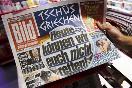 A man takes a copy of the German ''Bild'' newspaper from a stack in a newsagent in Berlin June 22, 2012. The headline reads, ''Bye, bye Greece. Today we won't be able to save you!''. Germany plays Greece on Friday in a quarter-final Euro 2012 soccer match. REUTERS/Thomas Peter