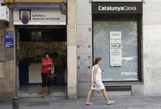 <p>Devant une succursale à Madrid de CatalunyaCaixa, l'une des quatres banques nationalisées (avec Bankia, NovaGalicia et Banco de Valencia) à qui la majeure partie de l'aide devrait bénéficier. L'Espagne a formellement sollicité lundi l'aide financière de la zone euro pour renflouer ses banques mais sans préciser le montant des capitaux dont elle a besoin. /Photo prise le 25 juin 2012/REUTERS/Andrea Comas</p>