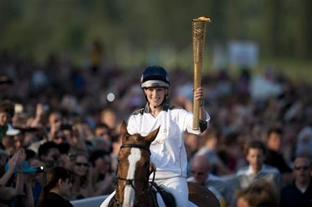 Zara Phillips holds the Olympic torch while riding through Cheltenham race course in Cheltenham May 23, 2012. REUTERS/Kieran Doherty