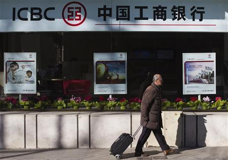 A man carries a case as he walks past the new branch of China's Industrial and Commercial Bank of China (ICBC) in central Madrid January 24, 2011. REUTERS/Juan Medina