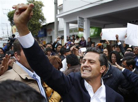 Enrique Pena Nieto, presidential candidate of the Institutional Revolutionary Party (PRI), waves to supporters before casting his vote in Atlacomulco July 1, 2012. REUTERS/Tomas Bravo