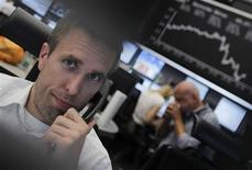 <p>Trader à la Bourse de Francfort. Loin de rassurer les marchés qui espéraient pourtant depuis des semaines une réponse au ralentissement de l'économie mondiale, les initiatives simultanées de trois grandes banques centrales ont affolé les investisseurs, qui y ont vu une confirmation de leurs craintes sur la dégradation de la conjoncture. /Photo prise le 5 juillet 2012/REUTERS/Alex Domanski</p>