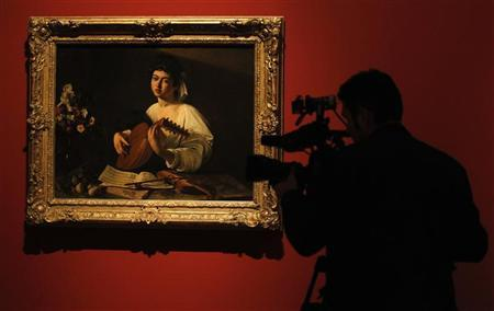 A cameraman films the ''Lute Player'', a painting by artist Michelangelo Merisi da Caravaggio, during the media preview of ''The Hermitage in the Prado'' exhibition at the Prado Museum in Madrid November 4, 2011. REUTERS/Andrea Comas