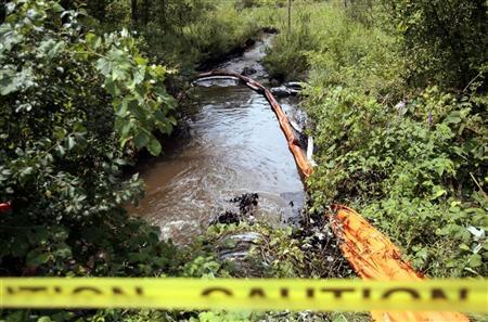 Yellow caution tape blocks off part of the Talmadge Creek where absorbent booms collect oil that is flowing into the Kalamazoo river after an oil pipeline, owned by Enbridge Energy Partners, leaked an estimated 820,000 gallons of oil into the Kalamazoo river in Western Michigan, near Marshall July 31, 2010. REUTERS/Rebecca Cook