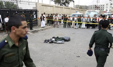 Policemen inspect the site of a suicide bombing outside the police academy in Sanaa July 11, 2012. At least 22 people were killed in a suicide bombing at a police academy in the Yemeni capital Sanaa on Wednesday, an attack, police investigators said bore the hallmarks of al Qaeda. REUTERS/Mohamed al-Sayaghi