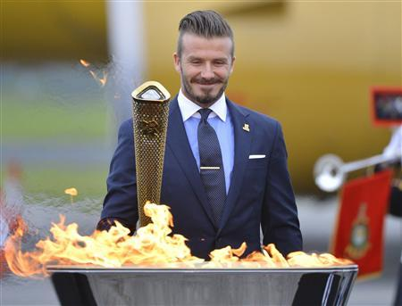 British soccer player and London 2012 Olympic Games ambassador David Beckham reacts after lighting the Olympic torch with a cauldron after arriving at RNAS Culdrose base near Helston in Cornwall, south west England in this May 18, 2012, file photo. REUTERS/Toby Melville/Files