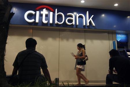 Pedestrians walk under a Citibank logo outside a branch in Singapore November 24, 2008. REUTERS/Vivek Prakash