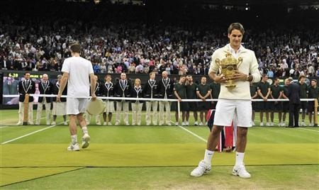 Roger Federer of Switzerland holds the winners trophy after defeating Andy Murray of Britain (L) in their men's singles final tennis match at the Wimbledon Tennis Championships in London July 8, 2012. REUTERS/Toby Melville