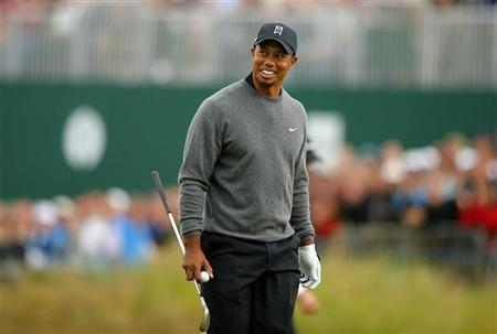 Tiger Woods of the U.S. walks off the 18th green after chipping in from a bunker to make birdie during the second round of the British Open golf championship at Royal Lytham & St Annes, northern England July 20, 2012. REUTERS/Brian Snyder