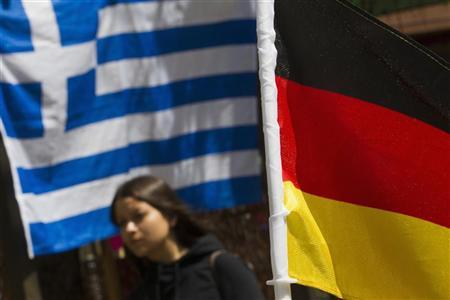 A woman walks past Greek and German national flags outside a Greek cafe in Berlin, June 22, 2012. REUTERS/Thomas Peter