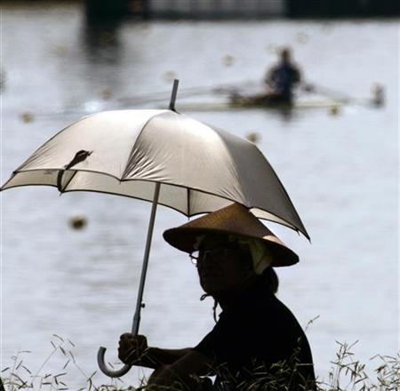 A spectator watching the World Rowing Championships wears a traditional Japanese hat and holds an umbrella while sitting in the hot summer sun in Gifu, Japan August 29, 2005. REUTERS/Andy Clark