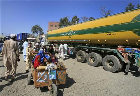 Men push a family past a fuel tanker, carrying supplies for NATO Forces, at the Pakistan-Afghan border of Torkham October 10, 2010. REUTERS/K. Parvez