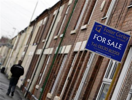 A man walks past a house for sale in Coalville, central England February 17, 2009. REUTERS/Darren Staples