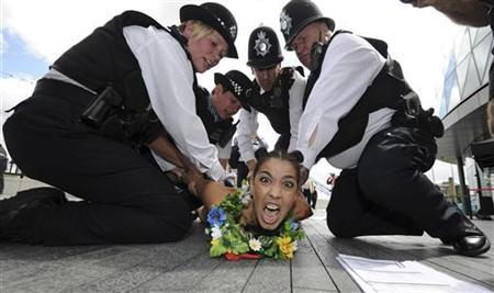 A Femen movement protestor is detained by police officers during a naked protest in London August 2, 2012. REUTERS/Paul Hackett