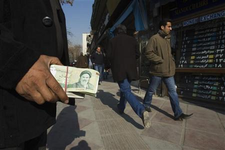 EDITORS' NOTE: Reuters and other foreign media are subject to Iranian restrictions on leaving the office to report, film or take pictures in Tehran. A money changer holds Iranian rial banknotes as he waits for customers in Tehran's business district January 7, 2012. REUTERS/Raheb Homavandi