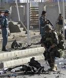 <p>Un soldado de la OTAN revisa el sitio donde ocurrió un ataque suicida con bomba en Kabul, sep 18 2012. Militantes afganos se adjudicaron el martes un ataque suicida contra un autobús que trasladaba a trabajadores extranjeros y que provocó la muerte de 12 personas en la capital de Afganistán, diciendo que fue una represalia contra un filme que se burla de Mahoma. REUTERS/Mohammad Ismail</p>