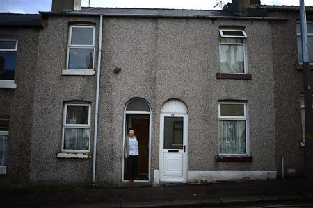 Jennie Iveson, aged 69, poses outside her terraced home in Barrow-in-Furness, northwestern England, September 26, 2012. Jennie, is Mitt Romney's fourth cousin. Not many people would associate Romney with Britain but it was in these rain-soaked plains of northern England that his ancestors lived for generations, converted to Mormonism and left for the U.S. in 1841 in search of the promised land. Romney is now one of the wealthiest Americans ever to run for the White House. Today, Washington's backrooms of power and intrigue are as far removed from the daily grind of his distant kin in Lancashire as one can imagine.   REUTERS/Dylan Martinez