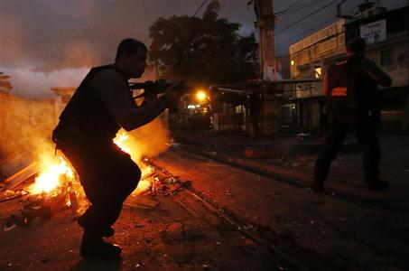 A policeman takes up position at the Jacarezinho slum during an operation to install Peacekeeping Unit riot police in Rio de Janeiro October 14, 2012. REUTERS/Sergio Moraes