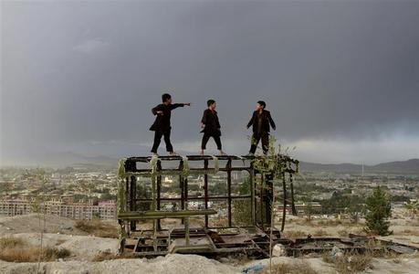 Afghan boys play on a destroyed car at a hilltop in Kabul October 18, 2012. REUTERS/Mohammad Ismail