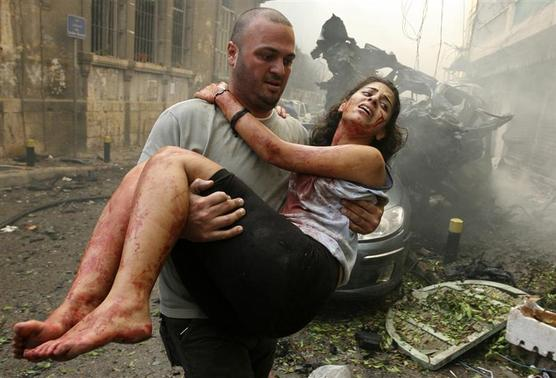 A wounded woman is carried at the site of an explosion in Ashrafieh, central Beirut, October 19, 2012. At least two people were killed and 15 wounded by a huge bomb that exploded in a street in central Beirut, witnesses and a security source said. REUTERS/Hasan Shaaban