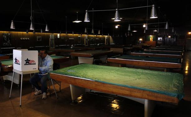 A voter casts his vote at Marie's Golden Cue pool hall during the U.S. presidential election in Chicago, Illinois, November 6, 2012. REUTERS/Jeff Haynes