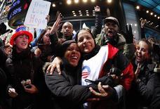 <p>Partisans de Barack Obama fêtant sa réélection, à Time Sqaure, à New York. Un regain d'optimisme sur une amélioration de la situation économique et une forte mobilisation des jeunes, des femmes et des membres des minorités favorables aux démocrates ont largement contribué à la victoire du président sortant. /Photo prise le 6 novembre 2012/REUTERS/Carlo Allegri</p>