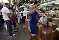 <p>Imagen de archivo de un vendedor en el mercado municipal de Sao Paulo, Brasil, feb 4 2012. Los precios al consumidor en Brasil subieron en octubre a su ritmo más alto desde abril, por un alza de los precios de los alimentos, según cifras del Gobierno, aunque una medida de costos mayoristas sugirió que la situación puede moderarse en los próximos meses. REUTERS/Nacho Doce</p>