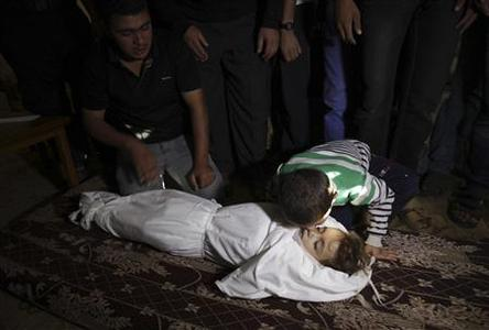 The brother of Palestinian boy Walid al-Abadlah, who according to hospital officials was killed in an Israeli air strike, kisses his body during his funeral in Khan Younis in the southern Gaza Strip November 15, 2012. REUTERS/Ibraheem Abu Mustafa