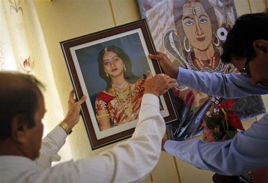 Andanappa Yalagi (L), father of Savita Halappanavar, is helped by a family friend as he hangs her portrait at their house in Belgaum in the southern Indian state of Karnataka November 16, 2012. Ireland's government pledged on Thursday to clarify its abortion laws after Halappanavar, who was refused a termination, died from blood poisoning in an Irish hospital. REUTERS/Danish Siddiqui