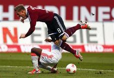 <p>Le joueur du Bayern David Alaba tente de prendre la balle à Sebastian Polter du FC Nuremberg (8). Le Bayern Munich a concédé samedi son premier match nul de la saison sur la pelouse de Nuremberg (1-1), redonnant ainsi un peu d'espoir à ses poursuivants. /Photo prise le 17 novembre 2012/REUTERS/Michael Dalder</p>