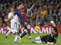 <p>Le Barcelonais Lionel Messi tente de tromper la vigilance du portier de Saragosse Roberto Jimenez. Le FC Barcelone a encore un peu plus creusé l'écart au sommet de la Liga espagnole, samedi, après sa victoire 3-1 face au Real Saragosse, avec un nouveau doublé de l'Argentin Lionel Messi à la clef. /Photo prise le 17 novembre 2012/REUTERS/Albert Gea</p>