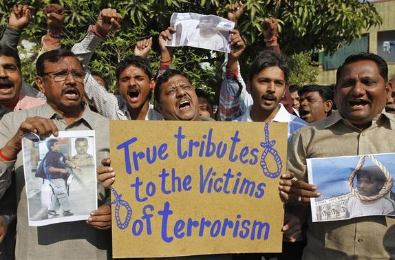 People hold a placard and pictures of Mohammad Ajmal Kasab, as they celebrate in Ahmedabad November 21, 2012. India executed Kasab, the lone survivor of a militant squad that killed 166 people in a rampage through the financial capital Mumbai in 2008, hanging him on Wednesday just days before the fourth anniversary of the attack. REUTERS/Amit Dave