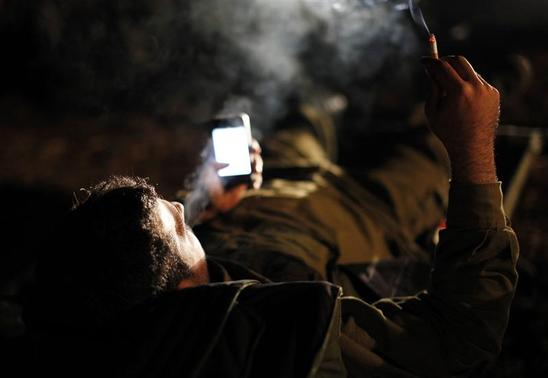 An Israeli soldier smokes a cigarette at a staging area outside the northern Gaza Strip November 21, 2012. REUTERS/Amir Cohen