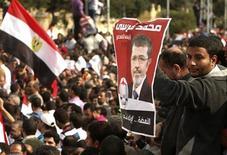 <p>Un seguidor del presidente egipcio Mohamed Mursi lleva un póster con la imagen del mandatario durante una manifestacioón en El Cairo. 23 de noviembre, 2012. El decreto del presidente de Egipto, Mohamed Mursi, para evitar que sus decisiones sean desafiadas por la justicia hasta que sea electo un nuevo Parlamento desató el viernes la furia de sus opositores, quienes lo acusaron de ser un nuevo Hosni Mubarak y de apoderarse de la revolución. REUTERS/Asmaa Waguih</p>