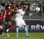 <p>Le Marseillais Jordan Ayew (à droite), auteur d'un but dimanche, aux prises avec le Lillois Aurélien Chedjou, lors de la victoire 1-0 du club phocéen au Vélodrome. Le PSG est apparu ce week-end avec Marseille comme le grand vainqueur de la 14e journée de Ligue 1 à l'issue de laquelle le club de la capitale a retrouvé son fauteuil de leader, à égalité de points avec l'OM. /Photo prise le 25 novembre 2012/REUTERS/Philippe Laurenson</p>