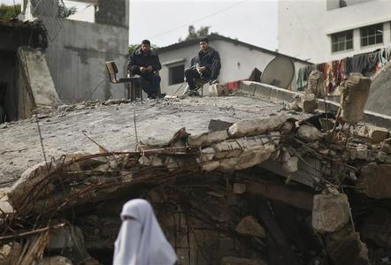 A Palestinian woman walks past as Hamas policemen sit atop their destroyed headquarters in Gaza City, November 25, 2012.REUTERS/Mohammed Salem